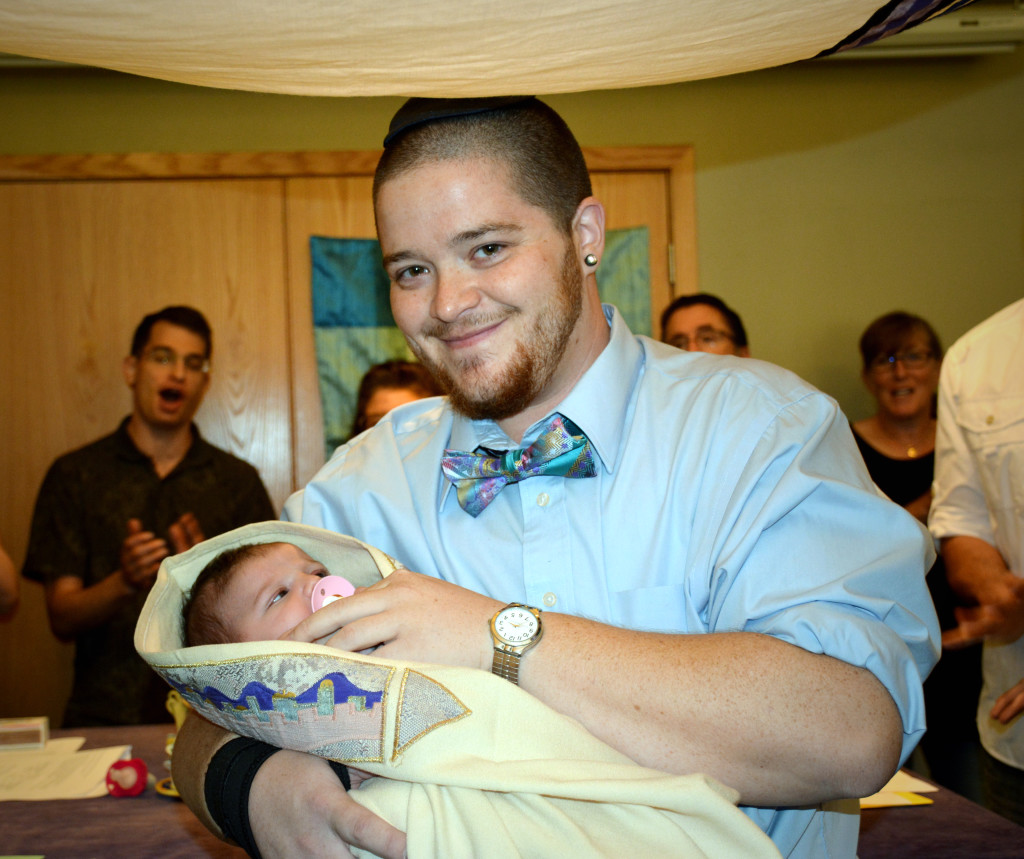 Rafi holds his daughter, Ettie, at her simchat bat Jewish welcoming ceremony in October. (Amy Ashford)