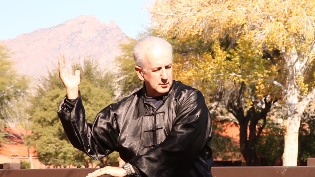 John Messing practices a tai chi movement.