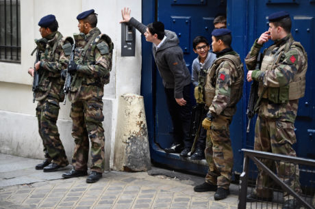 Children peer out from a doorway as armed soldiers patrol outside their school in the Jewish quarter of the Marais district in Paris, France, Jan. 13, 2015. (Jeff J Mitchell/Getty Images)