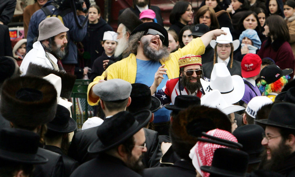 Jews dance in costumes and cowboy hats during Purim festivities in the Williamsburg section of Brooklyn on March 25, 2005 in New York City.  (Photo by Mario Tama/Getty Images)