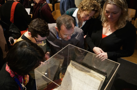 Attendees at an Amsterdam symposium on whether to lift the ancient order of excommunication against the philosopher Baruch Spinoza examining a copy of the original writ against him, Dec. 6, 2015. (Cnaan Liphshiz)
