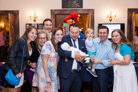 Seth Galena and Hindy Poupko, at his right shoulder, celebrate the birth of their son Akiva at his bris, June 15, 2014. (Piha Studio)