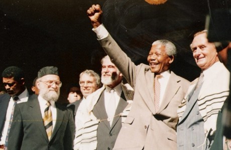 Nelson Mandela salutes the crowd at the Green and Sea Point Hebrew Congregation in Cape Town on a visit shortly after being elected South Africa's president in 1994. (Photo: SA Rochlin Archives, SAJBD) Joining Mandela, from left, are Rabbi Jack Steinhorn; Israel's ambassador to South Africa, Alon Liel; Chief Rabbi Cyril Harris; and Mervyn Smith, chairman of the South African Jewish Board of Deputies.